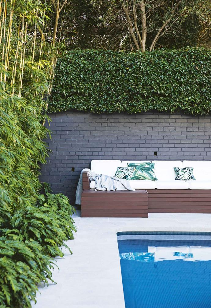 "[Screening](https://www.homestolove.com.au/how-to-create-privacy-with-screening-plants-6489|target=""_blank"") along the perimeter, and joining this garden with the pool area, is the vigorous Slender Weavers bamboo that replaced the old conifer hedge. Two stunning *Dracaena draco* (Dragon's Blood trees) standing boldly upright are justifiably the family's favourites. ""Viewed from the upper levels and uplit at night, they are a spectacular sight,"" says Oliver.<br><br>**Pool area** The wall, painted in dark Dulux Domino, recedes behind the abundant greenery. Cushions and pool equipment are housed under the spotted gum daybed. Pietra Di Loiano porcelain tiles in Settefonti from Rocks On surround the pool."