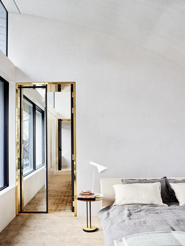 Transforming a former factory into his family home was pivotal, both personally and professionally, for architect Rob Mills. The bedroom walls are rendered and treated with stucco for a velvety finish which contrasts with the precision of the brass door frames. From *Belle* December/January 2017/18.