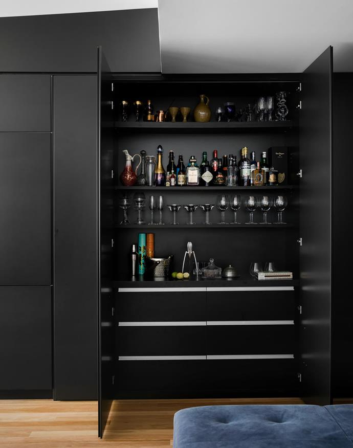 Wine storage and laundry utilities are located to the right of the cocktail cabinet.