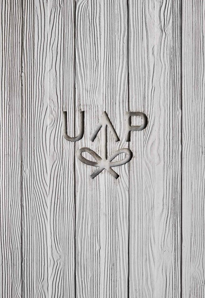 A board-marked concrete wall embossed with the United Places logo.