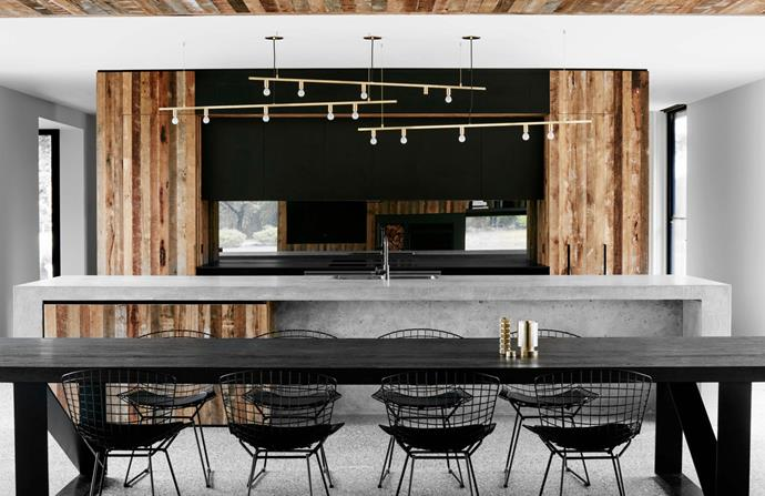 Above the kitchen island are Lambert & Fils 'Dot Line' suspension lights in brass. 'Bertoia' dining chairs from De De Ce.