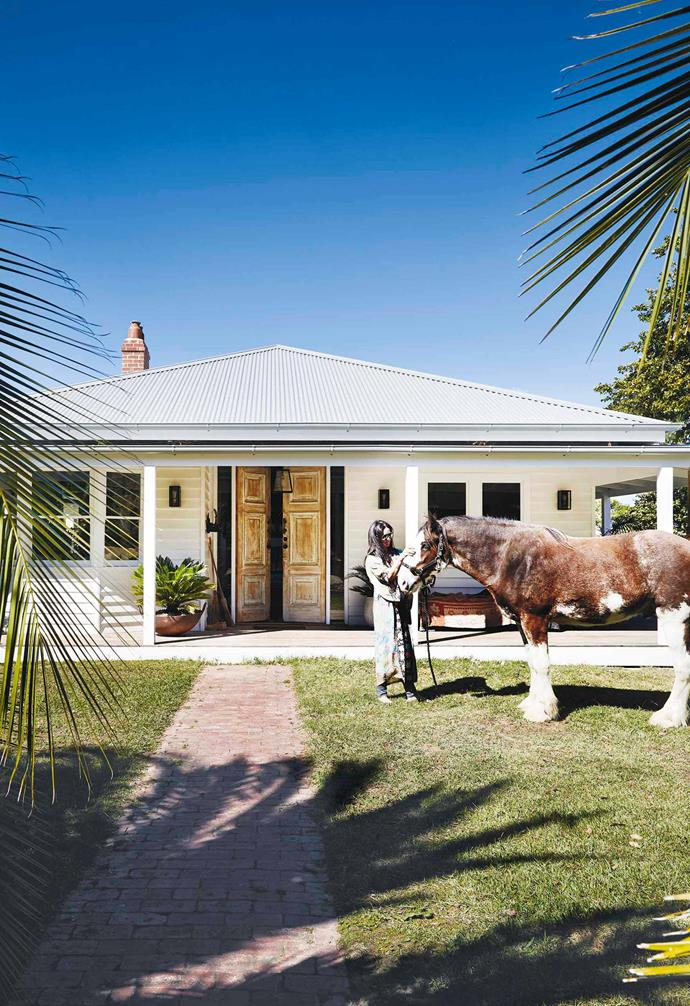 "**Exterior** Benny the Clydesdale greets homeowner Kerrie. She replaced the front door with reclaimed doors from an old courthouse, ""They were bottle green, so I sanded and whitewashed them, then added brass hardware I found in Bali,"" says Kerrie."