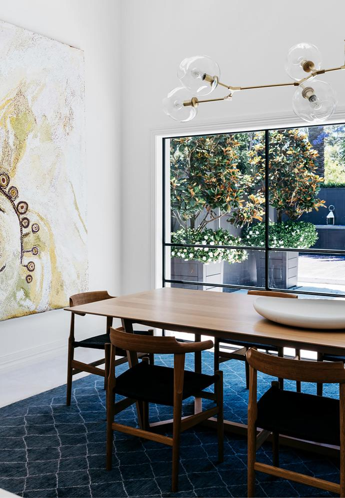 Custom 'Atticus' dining table by Lowe Furniture from Hub with Hans J. Wegner 'PP68' chairs from Great Dane on a 'Morocco' rug in Slate from Robyn Cosgrove. Lindsey Adelman pendant light. Artwork by Wawiriya Burton from Olsen Gallery.