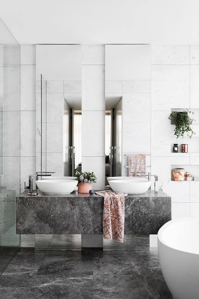 """The tall, thin mirrors in this [modern bathroom](https://www.homestolove.com.au/house-designed-for-an-odd-shaped-block-6069