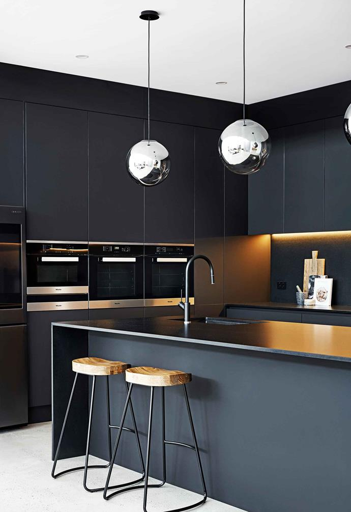 "**Pitch dark**<br><br>This black matte-finished cooking zone is anything but a shot in the dark. ""This kitchen was going to be the centrepiece of our home, so we knew we wanted it to be different,"" says owner Johnny Sekardi. The couple's key to success is considered lighting choices. LED strip lighting adds a subtle sheen to the cabinetry, while mirrored lamps from Beacon Lighting act as [task lighting](https://www.homestolove.com.au/task-lighting-ideas-20256