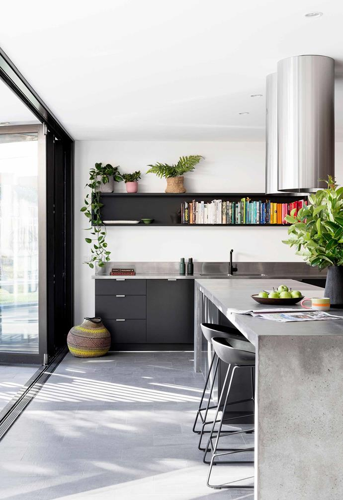 "**Starring steel** <br><br>While this home is not a converted factory or warehouse, it adopts a decidedly industrial-chic material palette in the kitchen space. A sculptural cylindrical rangehood sits above the custom concrete kitchen island becoming a striking statement. The brushed stainless steel look is echoed in the steel benchtop and [splashback](https://www.homestolove.com.au/kitchen-splashback-ideas-17258|target=""_blank"") throughout the rest of the kitchen.<br><br>"