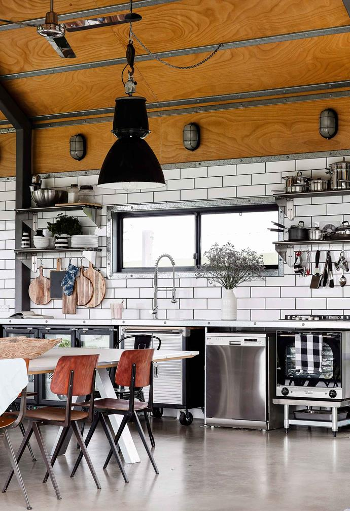 "**Lights up** <br><br>In this beachside retreat on NSW's South Coast the compact kitchen space features traditional white subway tiles with black grout, but is paired with concrete flooring and [stainless steel appliances](https://www.homestolove.com.au/colourful-kitchen-appliances-19988|target=""_blank"") and shelving. A sculptural industrial pendant lamp hangs above the dining space and works perfectly with vintage Czech factory wall lights.<br><br>"