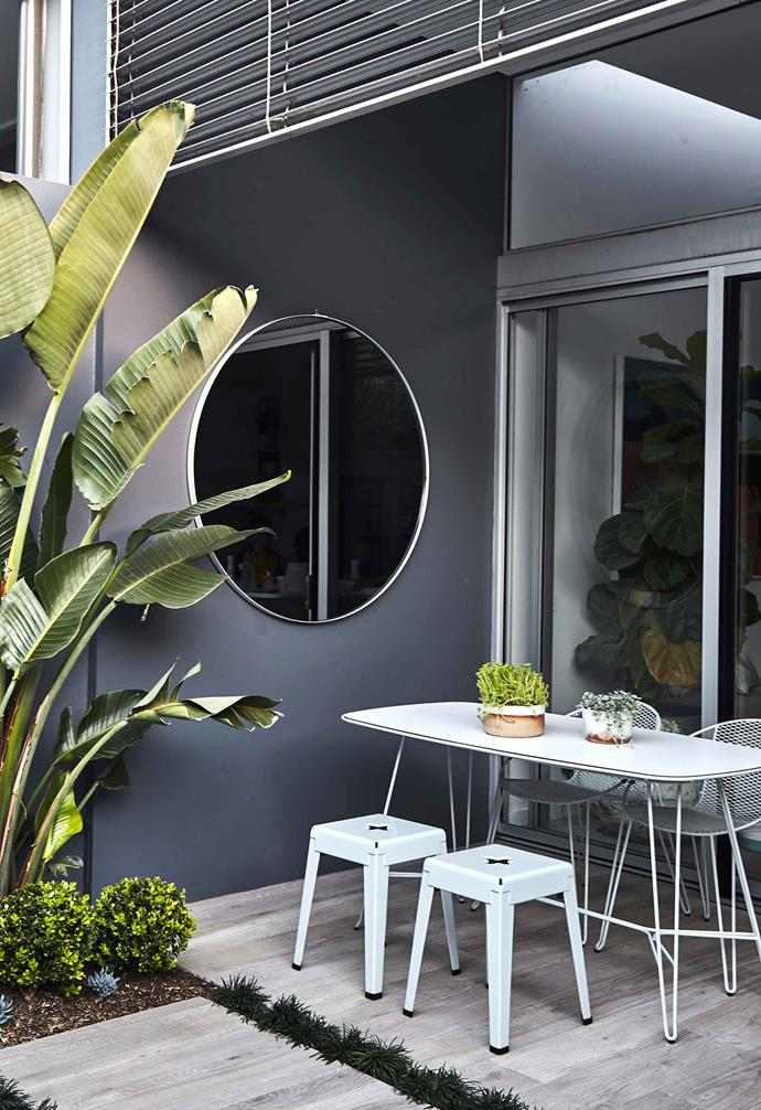 "A [large round mirror](https://www.homestolove.com.au/unique-mirror-designs-20361|target=""_blank"") in the corner reflects light and views as you move around the space. Volley outdoor dining table and chairs, and good one stools, all [Tait](https://madebytait.com.au/