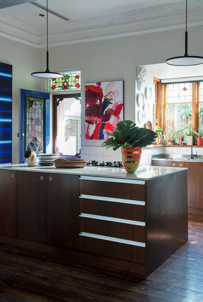Stained glass windows and colourful paintings provide light relief against the dark walnut cabinetry and floors. **Artwork:** Waldemar Kolbusz.