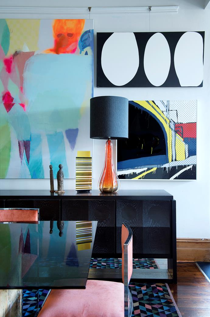 Ornamental objects on the black timber sideboard pick up on the vibrant shades in the artworks on the wall. **Artworks:** (left to right) Rhys Lee, Elisabeth Ford and Jasper Knight. **Yellow acrylic vessel** by BB Schmitt.