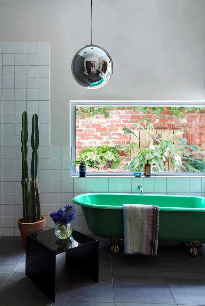 Green accents and a low-set window link the bathroom to the plant-filled courtyard outside.