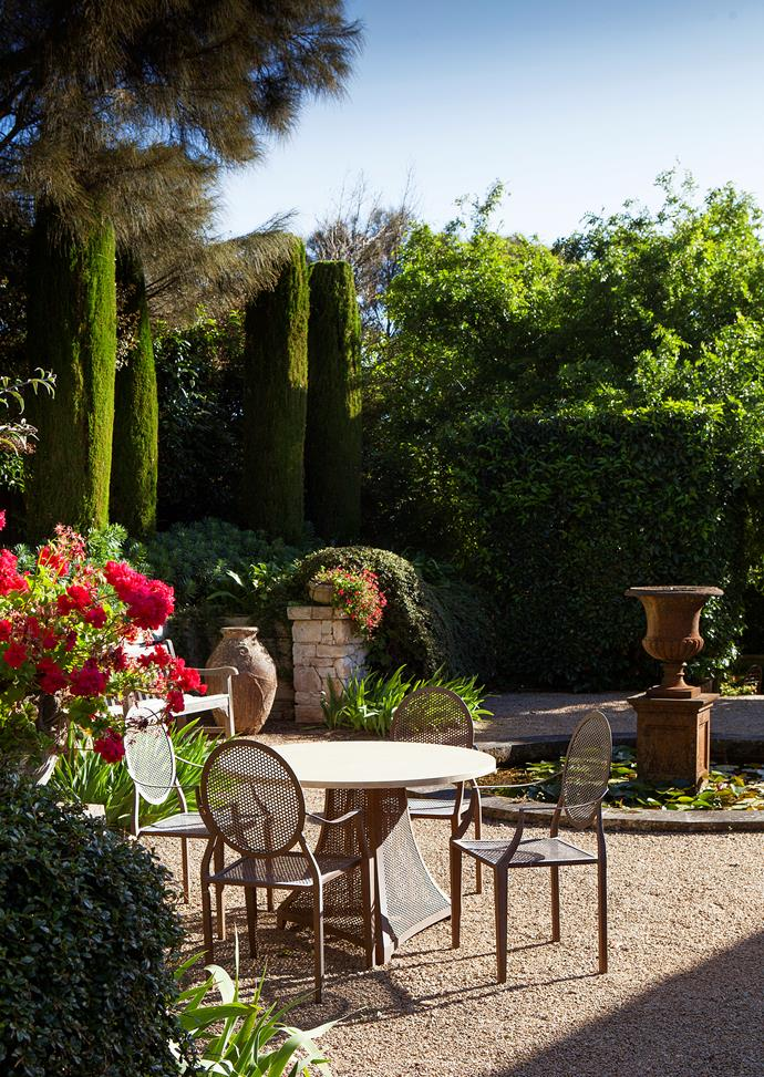 "The perfect [modern Mediterranean garden](https://www.homestolove.com.au/mediterranean-style-garden-in-the-mornington-peninsula-20372|target=""_blank"") sitting area: red geraniums spilling over the sandstone walls, massed iris in the gravel, and transplanted euphorbia under the conifers."