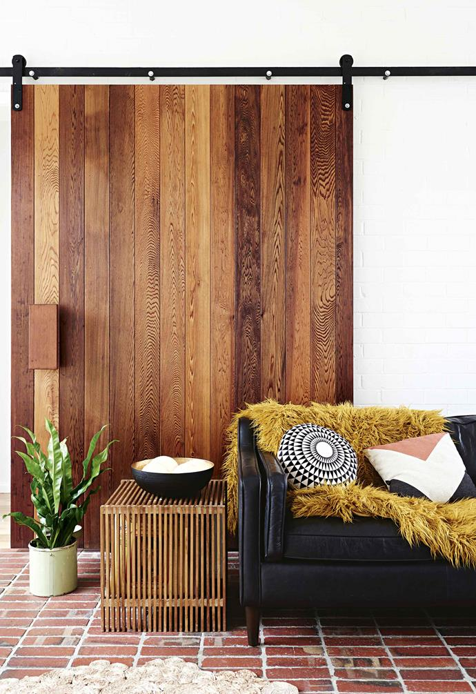 "A statement timber barn door was custom made to separate spaces in this [retro mid-century modern style home](https://www.homestolove.com.au/retro-mid-century-house-17593|target=""_blank""). The contrasting timber tones and grains create a dynamic visual effect."