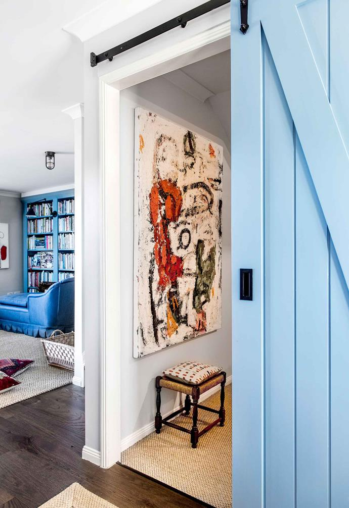"In [interior designer Bronnie Masefau's Brisbane home](https://www.homestolove.com.au/inside-an-interior-designers-brisbane-townhouse-20182|target=""_blank"") a bright blue bookshelf adds warmth to the living area. A small television room is concealed with a matching blue barn door with black hardware."