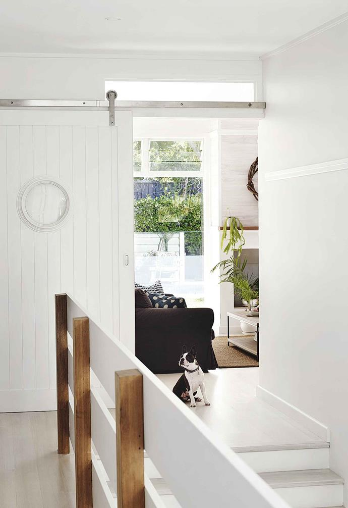 "[Coastal design meets Art Deco style in this weatherboard home](https://www.homestolove.com.au/coastal-art-deco-house-18746|target=""_blank"") that took just seven months to renovate. In keeping with the nautical theme throughout the home, a porthole window was embedded in this custom sliding barn door. Silver tracks and door hardware are a subtle contrast against the white door."