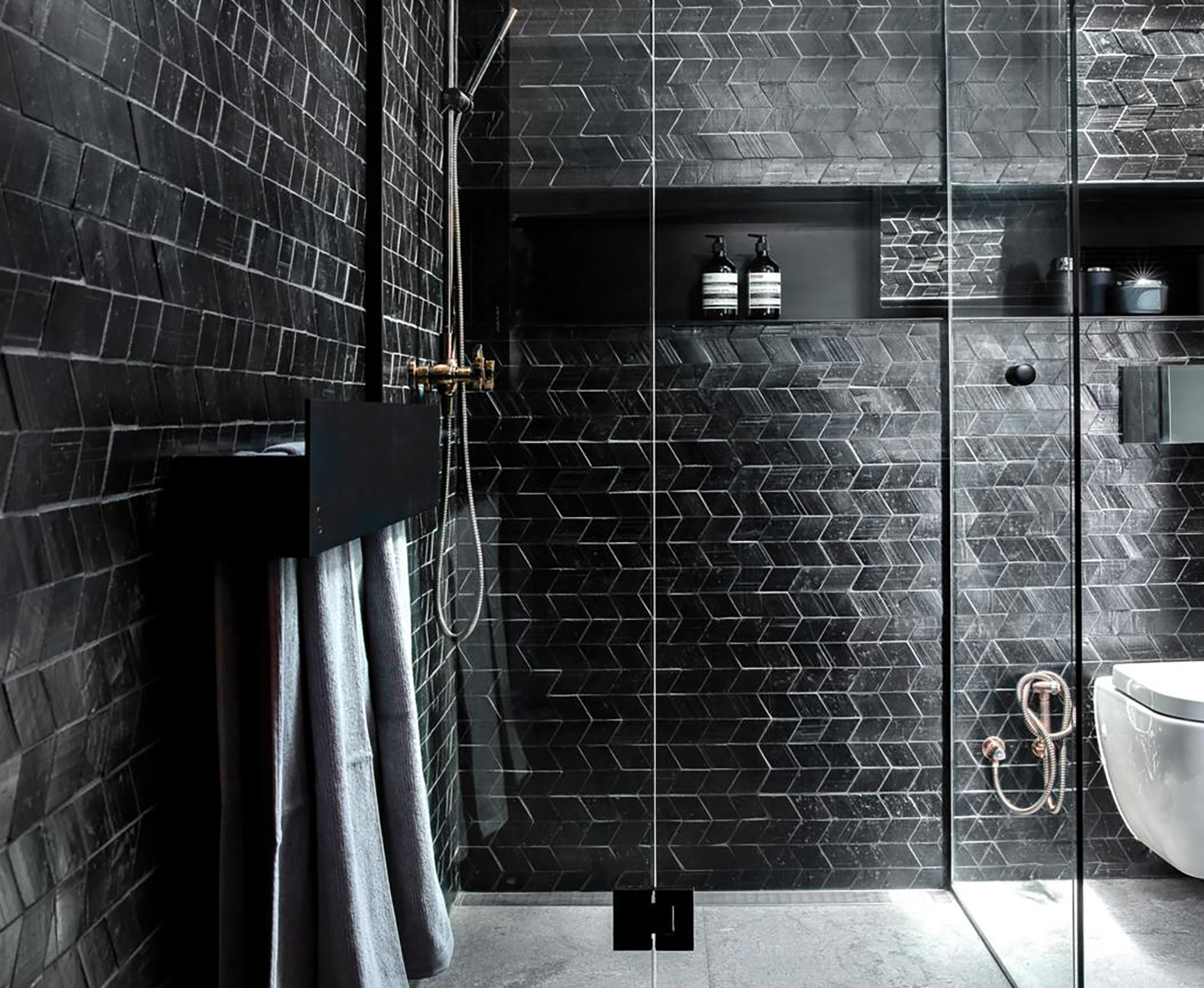 A moody bathroom with black tiles