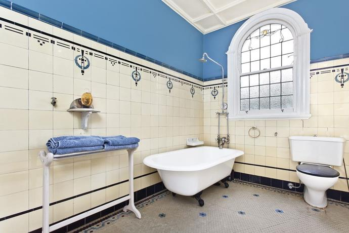 An Art Nouveau style bathroom featuring original tiles, stained glass windows and claw-footed tub.