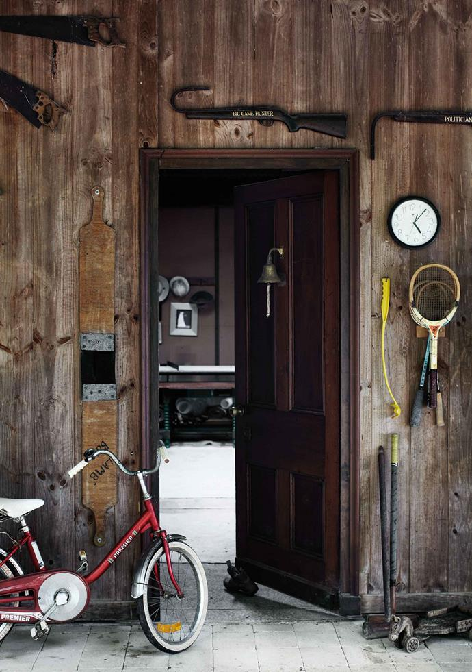 "The door to The Long Barn is decorated with farm tools, including old rifles and a wool paddle. The Long Barn is where Greg and Trish live, while their daughter Abbey and her family live in the main house. ""The main house is designed for a family, it really is a lovely home for kids,"" Greg says. ""We're about 100 metres apart, so we give each other some privacy. It's worked out really happily."""
