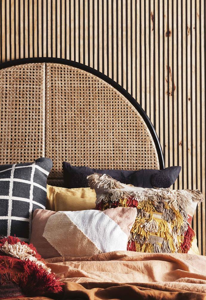 A woven cane bedhead is the hero piece of this relaxing bedroom space.