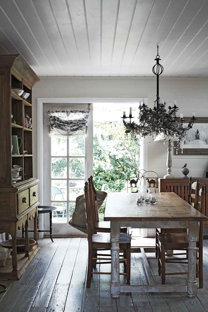 "The slab-laid stringybark floor was so warped that sanding was not an option. ""I abandoned the sander within 10 minutes, opting to limewash the floor instead,"" Rosie says. Wrap-around verandahs and a new roof completed the project. In the dining room a custom-made candelabra has been decorated with ivy and berries."