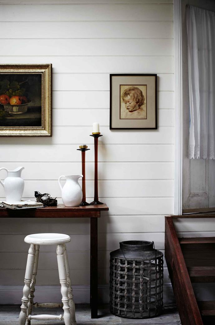 Inside, cherished pieces collected over the years create an airy decor. Clever use of mirrors aid light flow and simple window treatments include handmade blinds of French toile with Italian bobbles; trinkets gathered on her travels. Reminiscent of a Dutch master's painting, the entry hall is bathed in soft light from skylights in the roof.