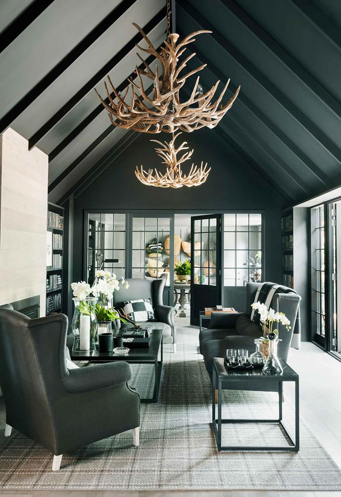 "In [Chyka Keebaugh's stunning Mornington Peninsula weekender](https://www.homestolove.com.au/mornington-peninsula-weekender-19583|target=""_blank"") a formal living room retreat has been painted in matt-black from pitched exposed beam ceiling to the walls, and then matched with black furniture and steel-framed doors. The ample natural light that enters the space prevents the room from becoming too dark."