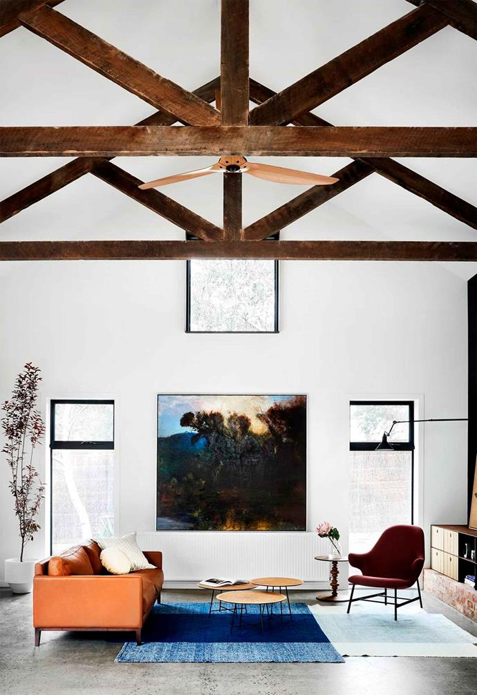 Dark timber exposed beams create a strong contrast against white walls and polished concrete flooring in this relaxed home.