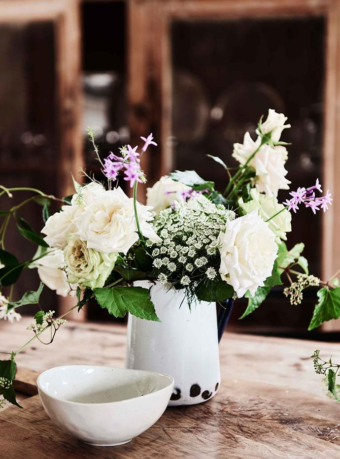 "An arrangement of freshly cut flowers in an [enamel jug](https://www.homestolove.com.au/enamel-homewares-13681|target=""_blank"") takes pride of place on the dining table.  The land surrounding Old Bogalara is a rose farm that Sus and Derek established soon after they moved in."