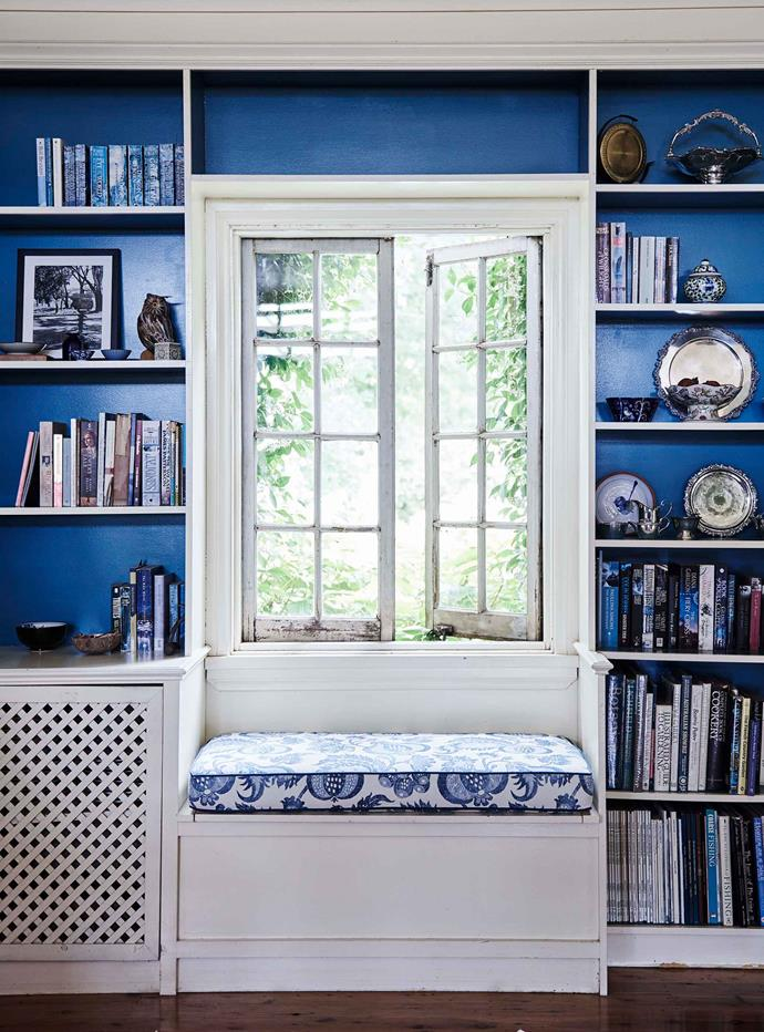 Vibrant blue shelving surrounds the window seat. On the shelves is the family's collection of heirloom silverware and favourite novels.