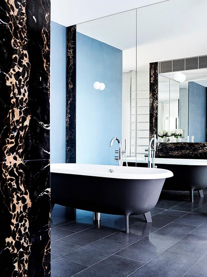 """Designer David Hicks says """"The main bathroom was to be hotel-like in its luxury but also beach-inspired. Dark stone floors offer respite from the constant light and sunshine. Portoro marble was used for its beautiful golden veining and dramatic dark base. Cerused timber was used on joinery while white-gloss Japanese tiles line the walls in the shower and toilet area. Blue frosted glass separates the dark-blue bath from the shower."""" From *Belle* October 2018."""