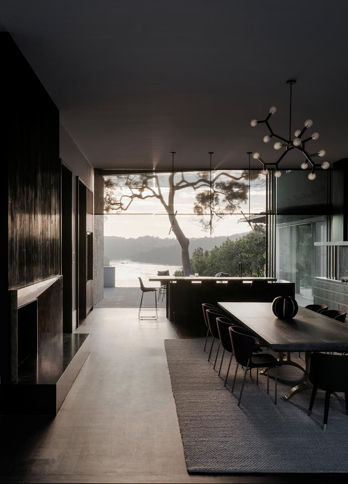 Looking through the dining area across the kitchen bench to the view of Sydney's Middle Harbour. Custom dining table by Dylan Farrell Design in ebonised and cerused oak with bronze cast and burnished legs. Friends & Founders 'La Pipe' chairs from Fred International with two Baxter carvers from Criteria. Light fitting is by Christopher Boots. The fireplace to the left has a hand-burnished brass surround.