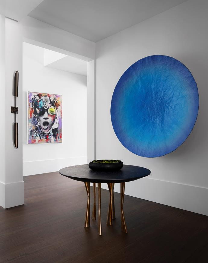 In the entrance is an 'Antler' table by Dylan Farrell Design for Jean de Merry. The blue artwork is by Ryan Hoffmann from Liverpool Street Gallery. Sconce is by Allied Maker. On the far wall is a work by Dain from Fillin Global, New York.