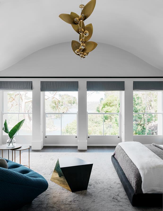 The main bedroom has a Ligne Roset 'Ploum' sofa in deep turquoise from Domo, gold octagonal table by Dylan Farrell Design and a set of RH nesting tables. The light fitting is by Rosie Li.