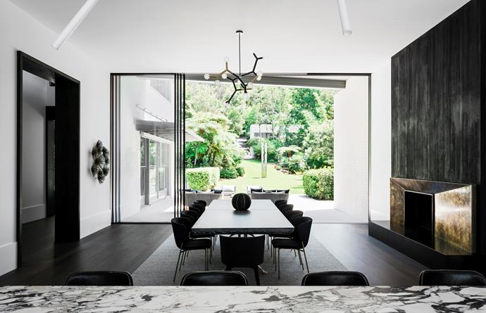 Looking through the dining area to the garden and pool area. Custom table by Dylan Farrell Design, Friends & Founders chairs from Fred International with Baxter carvers. Christopher Boots light fitting. Hand-burnished brass fireplace surround to the right.