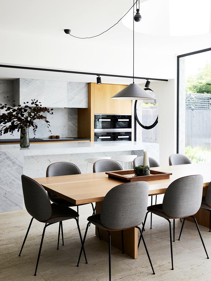 The textural splashback and rangehood cladding is made from a mix of Elba and Calacatta marble from RMS Stone. Rear bench is Neolith composite stone; island benchtop is Elba marble. Miele appliances. Qasair rangehood. Custom dining table, Made by Morgen. Gubi 'Beetle' dining chairs, and Hay 'About A Stool' stools, all Cult. Aggregato Salisceni pendant light, Artemide.