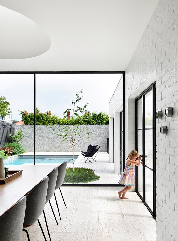 Floor-to-ceiling glazing maximises natural light at the south-facing rear of the home. Butterfly chairs, Angelucci 20th Century. Travertine flooring, CDK Stone (throughout).
