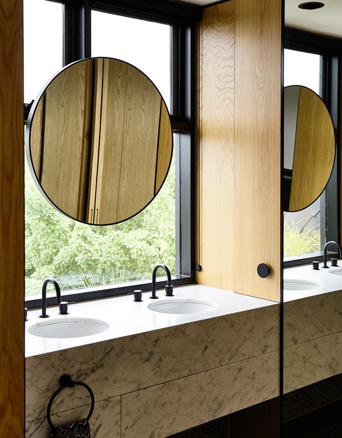 Mounting the mirror on the window frame allows light and green views in too. Carrara marble, RMS Stone. American oak joinery. Traccia basins, Astra Walker. Scala tapware and similar mirror, Reece.