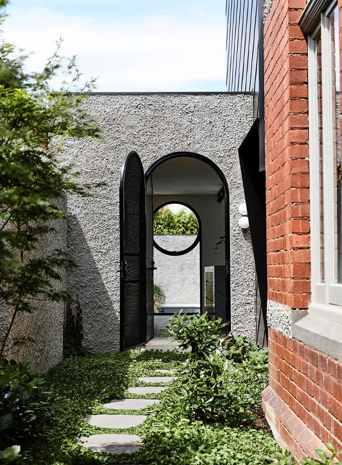 The lushly planted side entrance leads directly into the kitchen. Landscaping by Amanda Oliver Gardens. Dichondra creates a living carpet around slate steppers from Mintaro Quarries.
