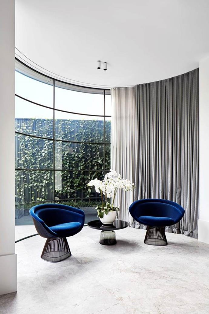 "A black lacquer ClassiCon 'Bell' side table sits between a pair of **Knoll 'Platner' chairs** in blue velvet. The curved lines of the furniture echo the steel-framed window in this section of the [living room](https://www.homestolove.com.au/two-storey-victorian-home-with-edgy-interior-melbourne-19201|target=""_blank""). Architecture by Nicholas Day. Interior design by Christopher Elliott Design. From *Belle* November 2018."