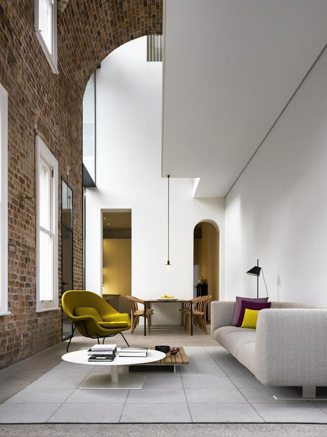Soaring ceilings and a brick barrel vault provide drama in this remodelled 1890s Sydney terrace house revamped by architect Renato D'Ettorre. In the ground-floor living-dining area is a **Knoll 'Womb' armchair**. From *Belle* February/March 2019.