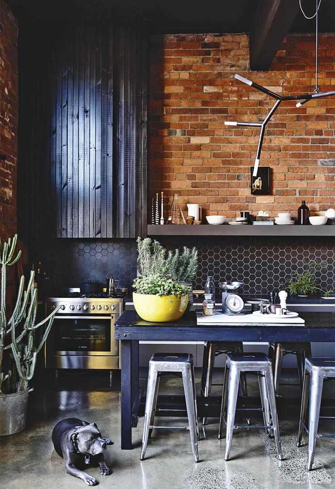 "This [former warehouse was converted into a moody industrial-chic loft-style home](https://www.homestolove.com.au/industrial-warehouse-home-melbourne-18326|target=""_blank"") and the original red bricks were left intact. [Gunmetal kitchen cabinets](https://www.homestolove.com.au/kitchen-cabinet-colour-ideas-17864