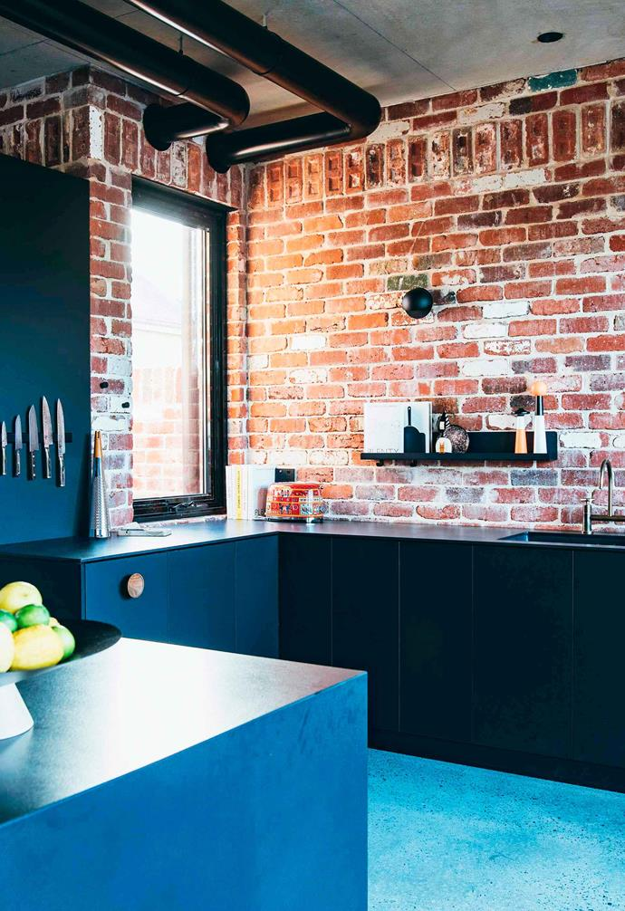 "Reclaimed red bricks from around the neighbourhood were used to build this new [industrial-style home in Perth](https://www.homestolove.com.au/brick-house-perth-19916|target=""_blank"") with the weathered patina of the bricks adding character to the house. In this kitchen space black cabinetry, a concrete-lined ceiling and polished concrete flooring combine to ensure that the bricks are the hero here."