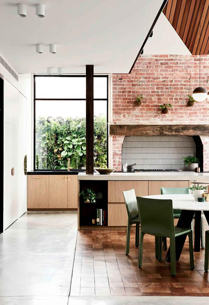 "This Melbourne home features an exposed brick wall in the kitchen which has been transformed into a striking architectural feature. The red bricks provide a dramatic contrast to vertical narrow subway tiles, the [concrete benchtop](https://www.homestolove.com.au/kitchen-benchtop-guide-19237|target=""_blank"") and timber cabinetry."