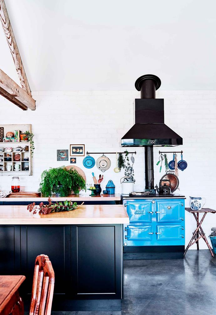 "The brick walls of this recycled brick home have been given a fresh coat of stark white paint, creating the perfect backdrop in this striking family home. In the kitchen dark [concrete floors](https://www.homestolove.com.au/concrete-floors-19778|target=""_blank"") are paired with black cabinetry and timber benchtops as well as a statement Esse wood combustion cooker in powder blue."