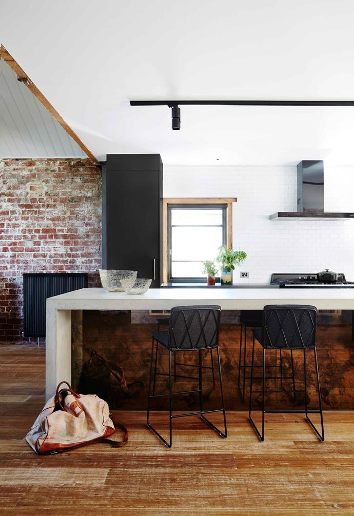 A former warehouse, this Melbourne home was converted with a modern industrial-style aesthetic. In the kitchen, the concrete benchtop is paired with an antique bronzed mirror base for the kitchen island. The exposed red brick wall has become the hero feature of this space.