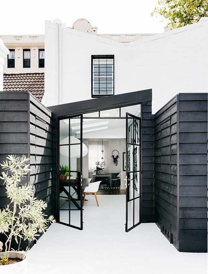 "Black steel frame doors connect the interiors to the roof deck of this [monochrome terrace home](https://www.homestolove.com.au/monochrome-makeover-of-sydney-terrace-4834|target=""_blank"") desgined by Pamela Makin."