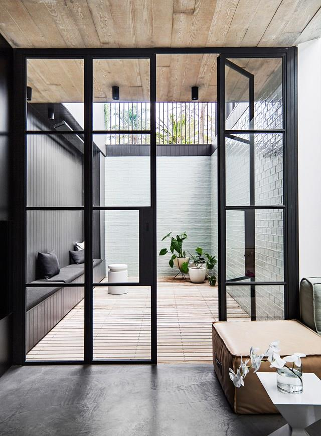 Steel-framed doors effectively divide the living room and internal courtyard while still allowing for light to fill the home.