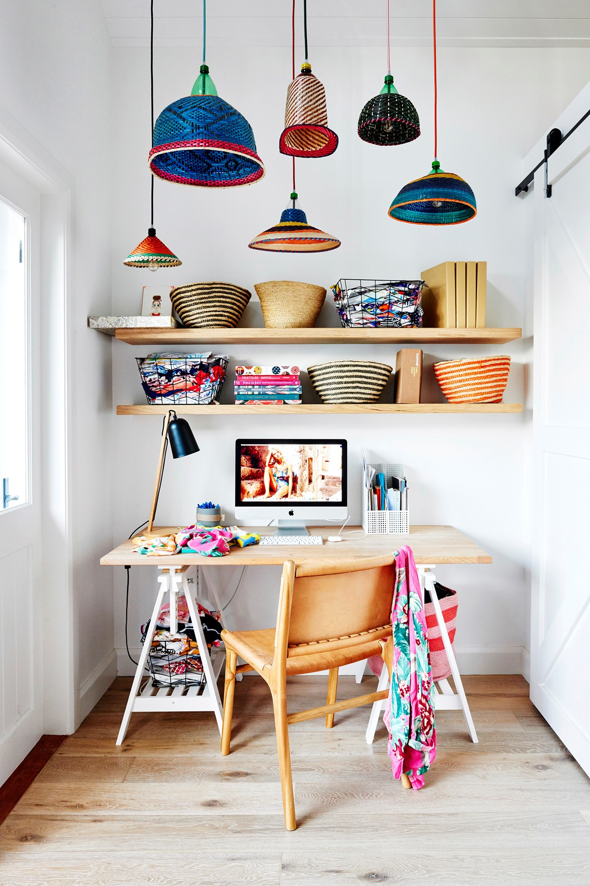 Talk about inspiring! This colourful home office would make working from home an absolute joy. A simple Ikea desk and leather chair from Barnaby Lane are both practical and stylish but the real stars are the custom oak shelving filled with woven baskets and assorted PET lamps from Safari Living.