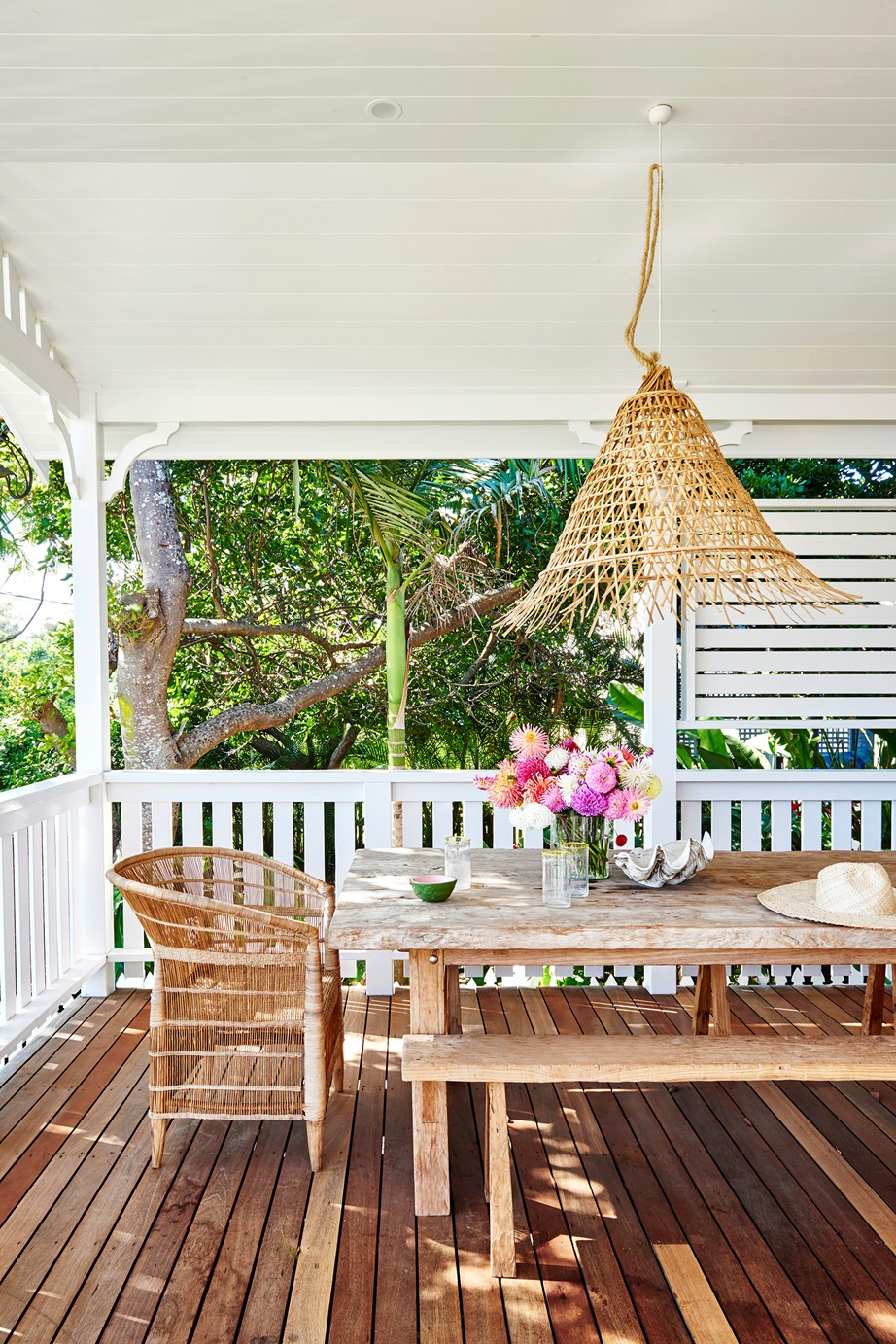 """A timber table and benches custom-made in Bali, paired with Malawi chairs from Greedilulu and a woven pendant from Bisque create a wonderfully laidback setting in this [Byron Bay home](https://www.homestolove.com.au/coastal-cottage-byron-bay-20442 target=""""_blank"""")."""