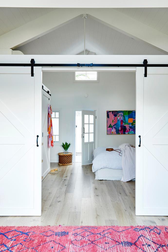 "The couple's builder custom-made [barn doors](https://www.homestolove.com.au/barn-door-17386|target=""_blank"") to close off the studio's bedroom. A bright artwork by Miranda Skoczek and Tigmi Trading rug provide the obligatory splashes of colour."